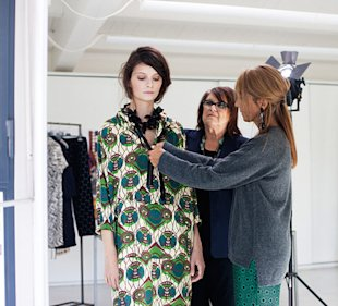 Marni's creative director Consuelo Castiglioni (right) dresses a model in her new collection while H&M's creative advisor Margareta van den Bosch looks on.