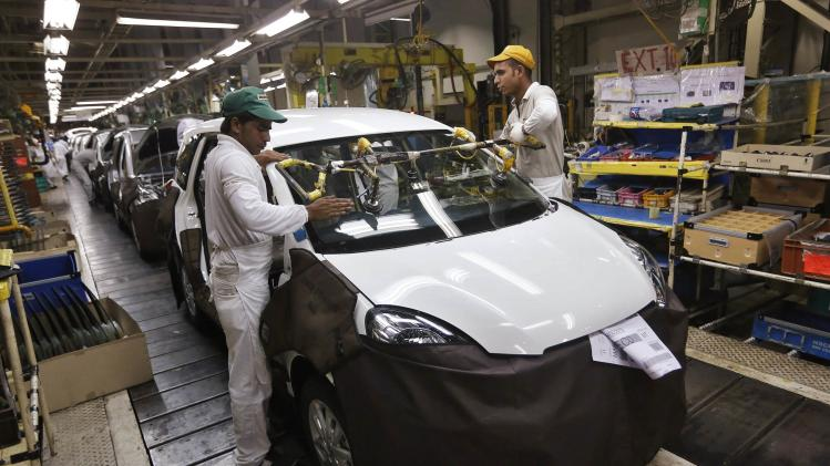 Employees install a windscreen on a Honda Mobilio car at the production line at a Honda plant in Greater Noida