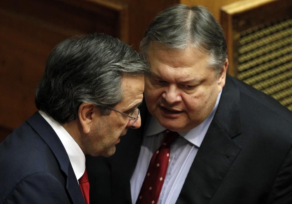 Greek Prime Minister Antonis Samaras, left, speaks with Socialist Leader Evangelos Venizelos at the Parliament during a debate on the new government's policy agenda before staging a vote of confidence in Athens, late Sunday July 8, 2012. (AP Photo/Kostas Tsironis)