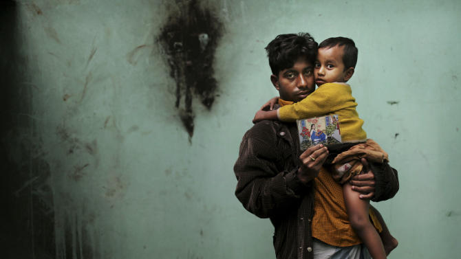 In this Friday, Dec. 21, 2012 photo, Bangladeshi Abdul Jabbar, 26, holds his son Masum, 18 months, as he displays a photograph of his wife Mahfouza Kahtun, 22, a sewing machine operator who died in the fire at Tazreen Fashions, in the garment district in Ashulia, near Dhaka, Bangladesh. When fire ravaged the Bangladeshi garment factory, killing 112 workers, dozens of their families did not even have a body to bury because their loved ones' remains were burned beyond recognition. Two months later, they have yet to receive any of the compensation they were promised - not even their relatives' last paychecks.  (AP Photo/Kevin Frayer)