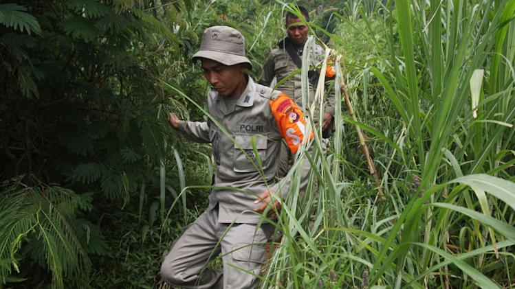 Indonesian police officers walks to the location of a plane crash in Salak mountain in Cijeruk,  Bogor, West Java, Indonesia, Friday, May 11, 2012. Rescue teams used climbing gear to scale the nearly sheer slopes of a dormant Indonesian volcano, hoping Friday to reach the wreckage of a Russian-made jetliner that crashed with 45 people aboard during a demonstration flight for potential buyers. (AP Photo/Achmad Ibrahim)