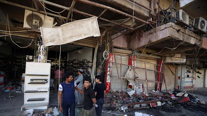 Civilians inspect the site of a bomb attack near restaurants and coffee shops filled with customers in central Baghdad's busy commercial Karradah neighborhood, Iraq, Sunday, May 3, 2015. Police say two bombs, one a suicide car bomb and the other a car bomb, went off just 10 minutes apart in the heart of Baghdad, and left more than a dozen civilians dead and others wounded, officials said. (AP Photo/Hadi Mizban)