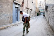 "A Syrian rebel carries a comrade who was wounded during clashes with government troops in Aleppo on July 31. Clashes erupted near two Christian areas of the Syrian capital Wednesday for the first time in the nearly 17-month uprising, as the battle for Aleppo entered its fifth day and President Bashar al-Assad hailed the ""heroic"" army"