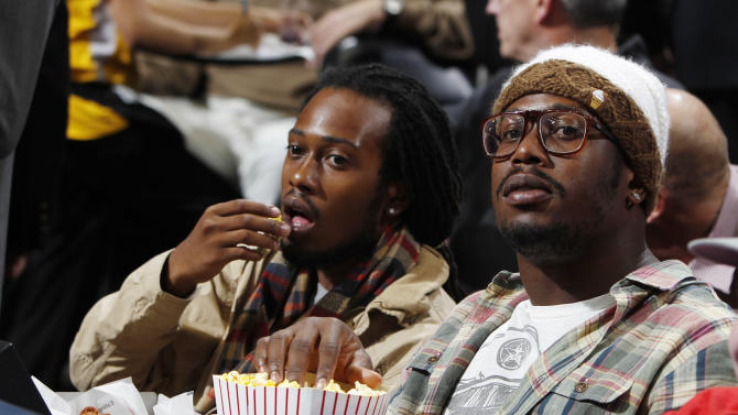 Denver Broncos linebacker Von Miller, right, looks on from a courtsie seat as the Miami Heat face the Denver Nuggets in the first quarter of an NBA basketball game in Denver on Thursday, Nov. 15, 2012. (AP Photo/David Zalubowski)