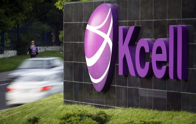 Vehicles drive past the KCell logo in front of the company's headquarters in Almaty