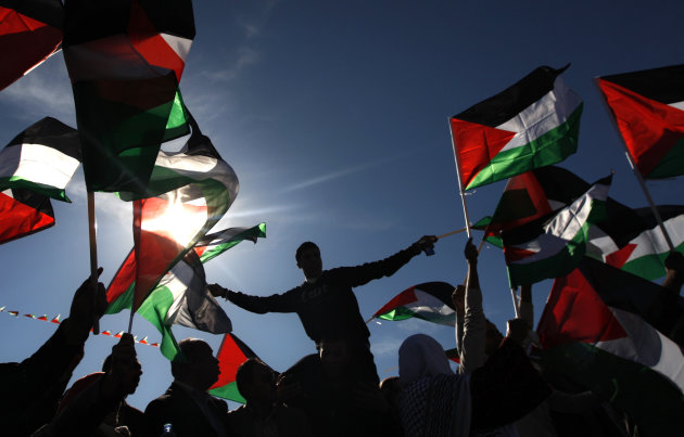 Palestinians wave flags as they celebrate their successful bid to win U.N. statehood recognition in the West Bank city of Ramallah, Sunday, Dec. 2, 2012. Palestinian President Mahmoud Abbas returned h