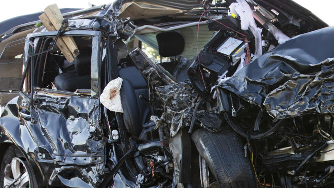 An automobile involved in a single-vehicle crash that took the lives of five people, including two children, near the Van Wyck Expressway rests on the flatbed of a New York Police Department tow truck, Sunday, July 22, 2012, in the Queens borough of New York. A New York Fire Department spokesperson stated that one person was critically injured and two others suffered serious injuries, all of whom were taken to Jamaica Hospital. (AP Photo/John Minchillo)