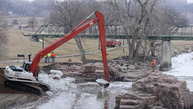 An excavator is used to break up a sheet of ice on the Big Sioux River, below the falls at Falls Park Friday, March 15, 2013, while crews work to recover the bodies of two adults that went into the water to rescue a 6 year old boy that fell into the water Thursday evening in Sioux Falls, S.D.  Sioux Falls Fire Chief Jim Sideras said early Friday a woman who a relative of the boy's but not his mother jumped into the water to try to save the boy, and a man jumped in to try to save the woman and child. The boy emerged from the water a short time later downstream at Falls Park, and was not injured.  (AP Photo/Argus Leader, Elisha Page) NO SALES