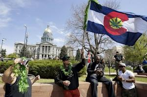 A man waves a Colorado flag with a marijuana leaf on it at Denver's annual 4/20 marijuana rally in front of the state capitol building