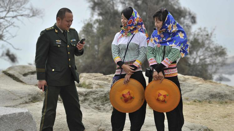 A People's Liberation Army officer looks at his mobile phone as he speaks with two Hui'an maiden tourist guides in Hui'an