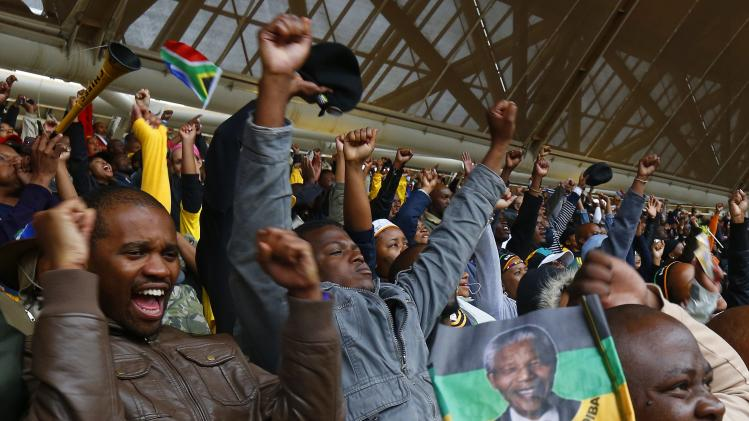 People sing the South Africa national anthem during the memorial service for late former South African President Mandela in Johannesburg