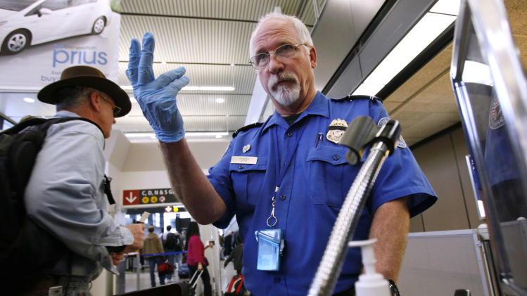 FILE - In this Jan. 4, 2010 file photo, TSA officer Robert Howard signals an airline passenger forward at a security check-point at Seattle-Tacoma International Airport in SeaTac, Wash. Flight attendants, pilots, federal air marshals and even insurance companies are part of a growing backlash to the Transportation Security Administration's new policy allowing passengers to carry small knives and sports equipment like souvenir baseball bats and golf clubs onto planes. (AP Photo/Elaine Thompson, File)