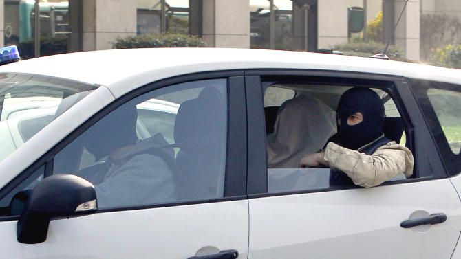 An unidentified man with his head covered, believed to be Abdelkader Merah or his companion, sits between masked police officers as they head to the French police's anti-terrorist headquarters in Levallois-Perret, outside Paris, Saturday, March 24, 2012. Merah's brother, Mohamed Merah is blamed for a series of deadly shootings which have shocked France and upended the country's presidential race. Merah, who claimed allegiance to al-Qaida, died in a hail of gunfire Thursday after a dramatic 32-hour-long standoff with law enforcement. (AP Photo/Christophe Ena, Pool)