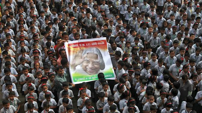 Teachers and schoolchildren hold a portrait of former Indian President Kalam during a prayer ceremony in Agartala
