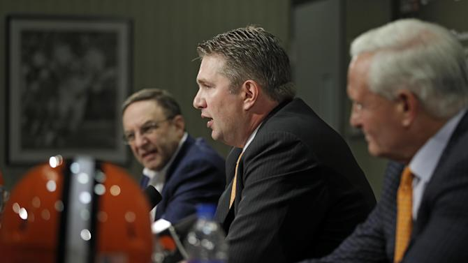 New Cleveland Browns head coach Rob Chudzinski, center, answers questions at his introductory news conference with CEO Joe Banner, left, and owner Jimmy Haslam at the NFL football team's practice facility in Berea, Ohio Friday, Jan. 11, 2013. Chudzinski becomes the 14th full-time head coach in team history. (AP Photo/Mark Duncan)