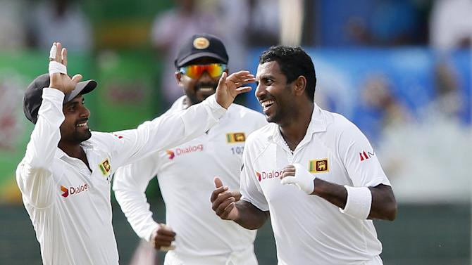 Sri Lanka's Prasad celebrates with his teammates Silva and Tharanga after taking the wicket of India's Pujara during the third day of their third and final test cricket match in Colombo