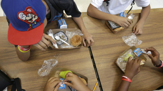 In this Sept. 4, 2013, photo, students at the Maurice J. Tobin K-8 School in Boston's Roxbury neighborhood eat free lunches consisting of a sandwich with meat, a vegetable dish, a piece of fruit, and milk. Boston Public Schools officials say 76 percent of students already qualified for free or reduced price meals, and this program to provide all students with free breakfast and lunch will cut down on district paperwork and expenses. (AP Photo/Steven Senne)