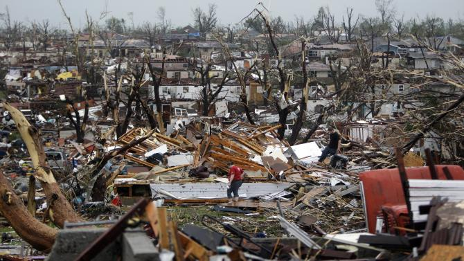Meghan Miller stands in the middle of a destroyed neighborhood as she checks on her sister-in-law's home Monday, May 23, 2011, in Joplin , Mo. A large tornado moved through much of the city Sunday, damaging a hospital and hundreds of homes and businesses. (AP Photo/Jeff Roberson)