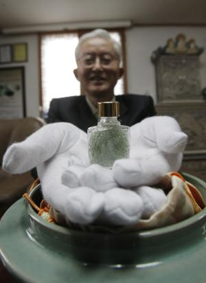 """In this Wednesday, Oct. 12, 2011 photo, Kim Il-nam, a retired high school principal, displays a small glass bottle containing beads made from his father's ashes during an interview in Icheon, South Korea. Kim dug up his father's grave, cremated his bones and paid $870 to have the ashes transformed into gemlike beads. """"Whenever I look at these beads, I consider them to be my father and I remember the good old days with him,"""" Kim said. (AP Photo/Ahn Young-joon)"""