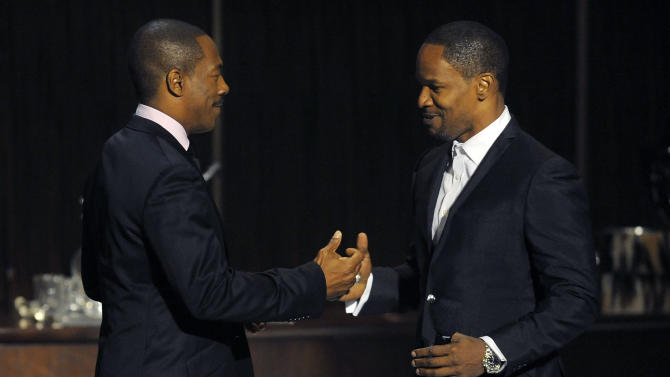 """Eddie Murphy, left, is greeted by Jamie Foxx onstage at """"Eddie Murphy: One Night Only,"""" a celebration of Murphy's career at the Saban Theater on Saturday, Nov. 3, 2012, in Beverly Hills, Calif. Foxx and Murphy were cast members in the 2006 film """"Dreamgirls."""" (Photo by Chris Pizzello/Invision)"""