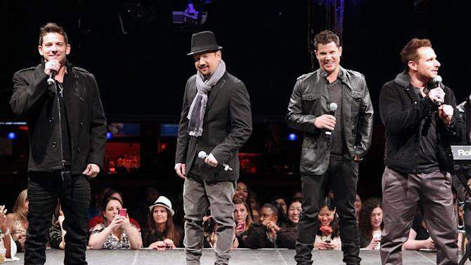 """In this picture provided by Starpix, from left, Jeff Timmons, Justin Jeffre, Nick Lachey, and Drew Lachey of 98 Degrees perform during the announcement of """"The Package Tour"""", Tuesday, Jan. 22, 2013 in New York. The major summer tour will feature New Kids on the Block, 98 Degrees and Boyz II Men. (AP Photo/Starpix, Kristina Bumphrey)"""