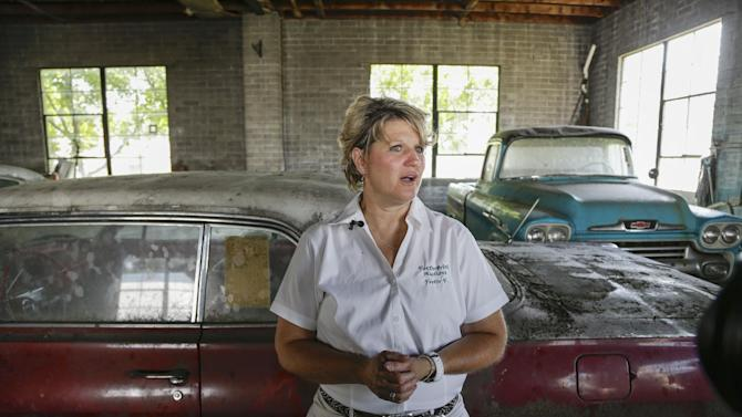 In this Aug. 12, 2013 photo, auctioneer Yvette VanDerBrink stands in front of a brand new, old 1963 Chevrolet Impala and a brand new, old 1958 Cameo pickup truck, right, at the former Lambrecht Chevrolet car dealership in Pierce, Neb. Next month, bidders from at least a dozen countries and all 50 U.S. states will converge on Pierce, a town of about 1,800 in northeast Nebraska, for a two-day auction that will feature about 500 old cars and trucks, mostly Chevrolets that went unsold during the dealership's five decades in business. About 50 have fewer than 20 miles on the odometer, and some are so rare that no one has established a price. The most valuable could fetch six-figure bids. (AP Photo/Nati Harnik)