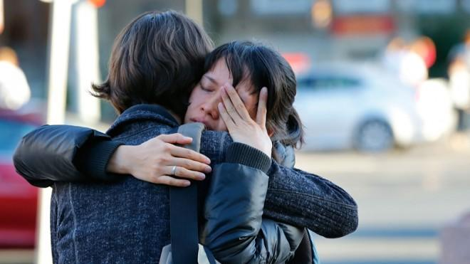 Boston University students hug following a service for graduate student Lu Lingzi, who was killed at the Boston Marathon.