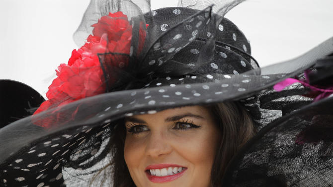 Amanda Lear, from Ruby, S.C., watches horses in the paddock area before the 138th Kentucky Derby horse race at Churchill Downs, Saturday, May 5, 2012, in Louisville, Ky. The Run for the Roses draws them to Churchill Downs. But what race goers wear is as much a spectacle in itself. (AP Photo/Mark Humphrey)