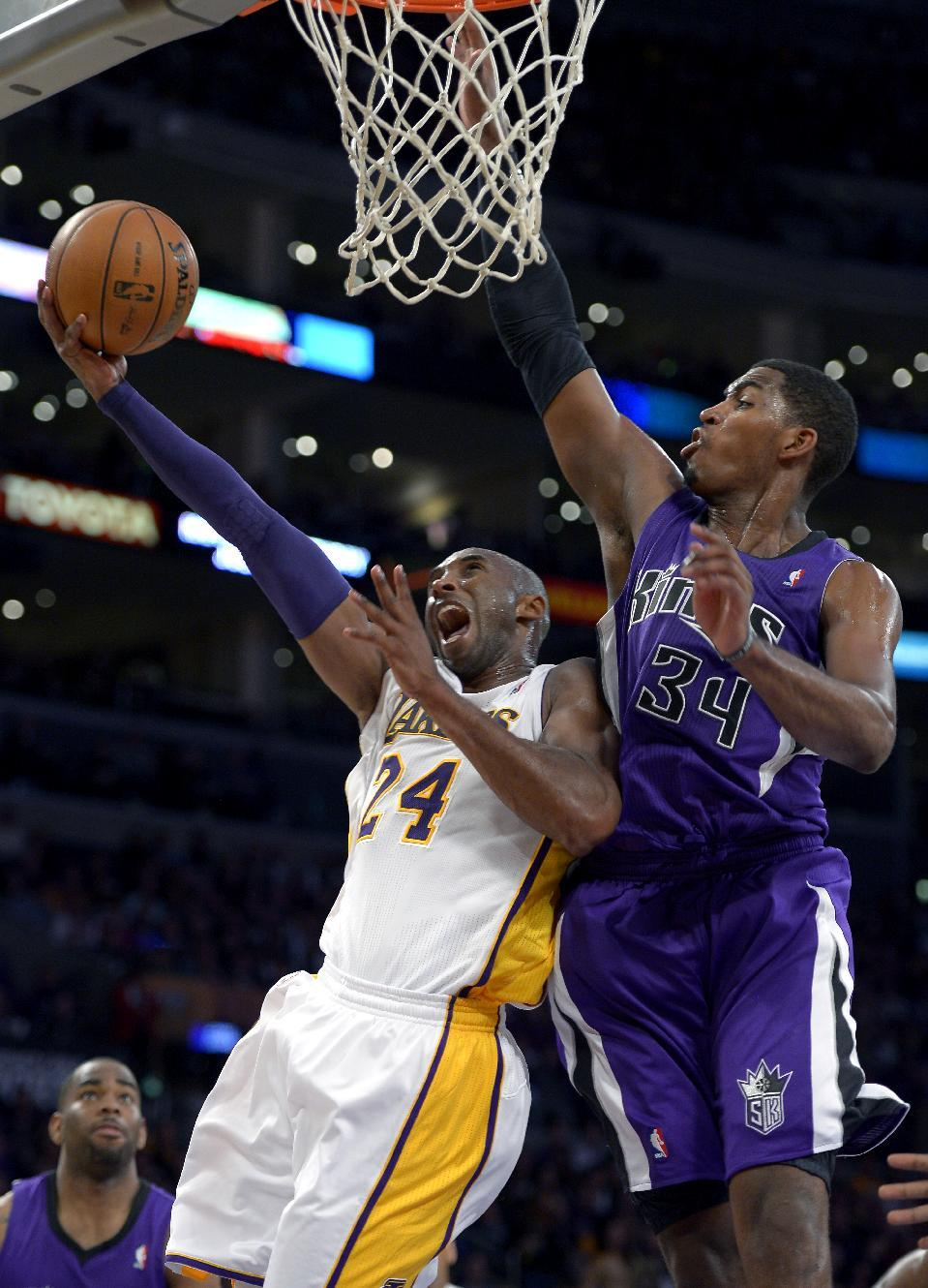 Los Angeles Lakers guard Kobe Bryant, left, puts up a shot as Sacramento Kings forward Jason Thompson defends during the second half of their NBA basketball game, Sunday, Nov. 11, 2012, in Los Angeles. The Lakers won 103-90.  (AP Photo/Mark J. Terrill)