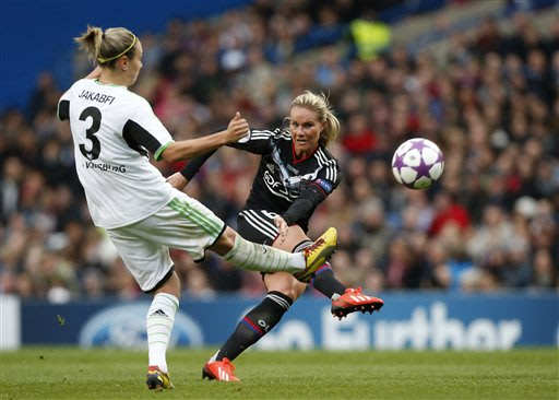 Lyon's Amandine Henry, right, shoots past Wolfsburg's Zsanett Jakabfi during the women's Champions League final soccer match between Wolfsburg and Olympique Lyonnais at Stamford Bridge Stadium in Lond