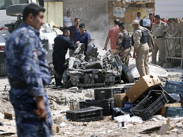 Security forces inspect the scene of a car bomb attack in Basra, 340 miles (550 kilometers) southeast of Baghdad, Iraq, Sunday, Sept. 9, 2012. In violence, which struck at least 10 cities across the nation Insurgents killed at least 39 people in a wave of attacks against Iraqi security forces on Sunday, gunning down soldiers at an army post and bombing police recruits waiting in line to apply for jobs, officials said. (AP Photo/Nabil al-Jurani)