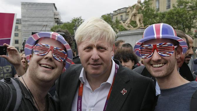 London Mayor Boris Johnson, center, poses for pictures with fans of Britain's team following a photo-op with London ambassadors, the volunteers working around the city to give tourists directions and information, in central London, Tuesday, July 31, 2012. After meeting Tuesday with the volunteers, Johnson firmly denied media reports that he was trying to capitalize on the goodwill churned up by the games to catapult himself into the prime minister's chair.  (AP Photo/Lefteris Pitarakis)