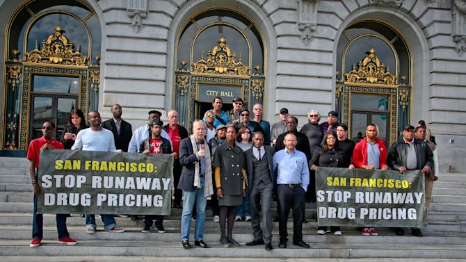 """IMAGE DISTRIBUTED FOR AIDS HEALTHCARE FOUNDATION - (left to right in the center, front row) Ged Kenslea, Dr. Lisha Wilson, Jesse Brooks, Dale Gluth and advocates from AIDS Healthcare Foundation and other groups announce the launch of a new ballot initiative to rein in drug pricing on the steps of San Francisco City Hall on Thurs., Nov. 15, 2012 in San Francisco.  Signature gathering in the city starts this week for the measure, which directs city officials to, """"…employ all opportunities that the municipal government possesses to bring down the price of prescription drugs.""""  (John Storey/AP Images for AIDS Healthcare Foundation)"""