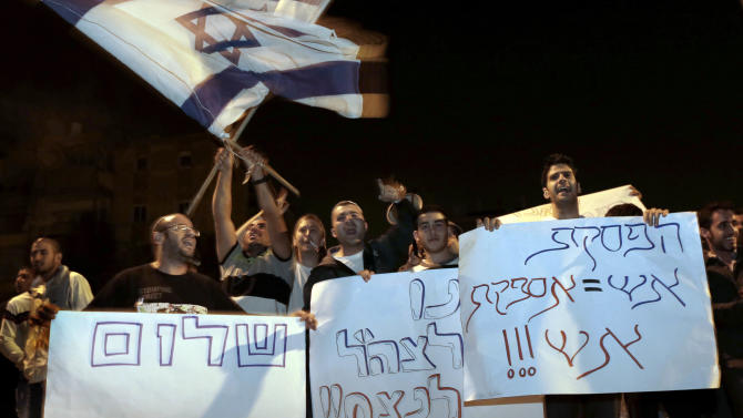 "FILE - In this Nov. 21, 2012 file photograph, Israelis hold signs and flags as they protest the cease-fire in the southern Israeli city of  Kiryat Malachi.  Hebrew on signs from right read: ""Cease-fire = supply of fire"", ""Let the IDF win"" and ""False peace"". (AP Photo/Tsafrir Abayov, File)"