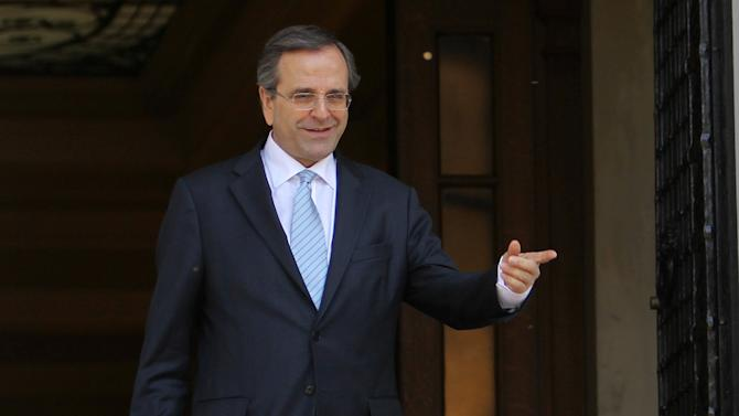 Greek Prime Minister Antonis Samaras welcomes recently-elected Cypriot President Nicos Anastasiades, not seen, at his official residence in Athens on Monday, March 11, 2013. Updated official data show Greece's economy shrank at a slightly slower pace than initially forecast in the last quarter of 2012, but still contracted by 6.4 percent during the year. (AP Photo/Thanassis Stavrakis)