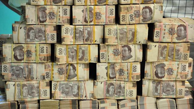 FILE - In this May 22, 2013 file photo, bundles of 500 peso bills are displayed to the press after they were found at the offices of a former state official in the capital city of Villahermosa, Tabasco state, Mexico. The cash was found in an office of Jose Saiz, who was finance secretary under former Gov. Andres Andres Granier of Pena Nieto's Institutional Revolutionary Party (PRI). Granier, the former governor of southern Tabasco state, was charged this week with money laundering and embezzlement and woke up Wednesday, June 26, 2013 in a Mexico City prison. (AP Photo/America Rocio, File)