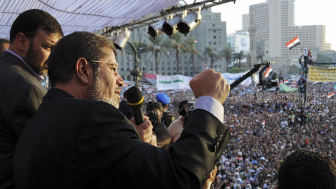 In this image released by the Egyptian Presidency, Egyptian President-elect Mohammed Morsi speaks to supporters at Tahrir Square in Cairo, Egypt, Friday, June 29, 2012.  In front of tens of thousands of cheering supporters, Egypt's first Islamist and civilian president-elect vowed Friday to fight for his authority and symbolically read an oath of office on Cairo's Tahrir Square on the eve of his official inauguration.(AP Photo/Mohammed Abd El-Maaty, Egyptian Presidency)
