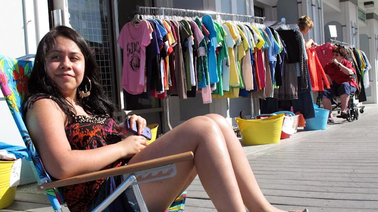 In this April 17, 2012, photo, Sayuri Torrealba sits on the boardwalk at her clothing boutique in Belmar N.J. She says the unseasonably warm spring weather has business at her shop up 30 percent over what it normally would be at this time of year. (AP Photo/Wayne Parry)