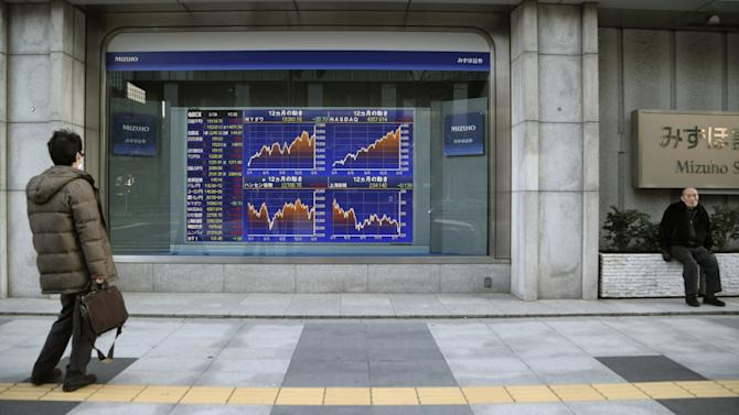 A man looks at an electronic stock board of a securities firm in Tokyo, Thursday, March 6, 2014. Shares were mostly higher in Asia on Thursday as the standoff over Ukraine between Russia and the West continued to ease and the yen weakened. (AP Photo/Koji Sasahara)