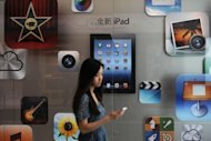 A customer passes an Apple store in Shanghai on July 20. Apple reported a rise in its quarterly profit to $8.8 billion on hot iPad sales but the results came up short of lofty Wall Street expectations, prompting its shares to dive