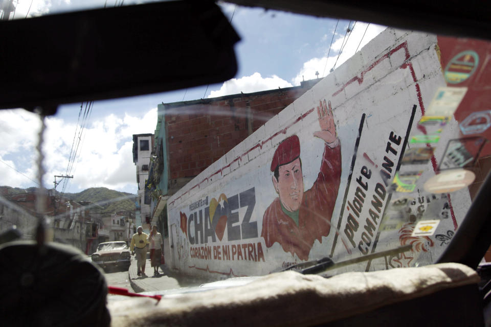 "The windshield of a car frames a mural of Venezuela's President Hugo Chavez in Caracas, Venezuela, Wednesday, Jan. 2, 2013.  Venezuela's Vice President Nicolas Maduro is returning home Wednesday from a visit with Chavez in Cuba and says the ailing president's condition remains ""delicate"" three weeks after his cancer surgery. (AP Photo/Ariana Cubillos)"