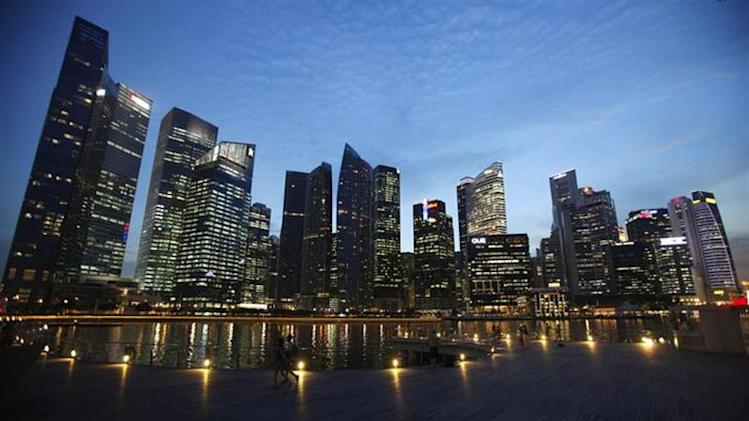 People walk past the skyline of Marina Bay central business district in Singapore April 26, 2013. REUTERS/Edgar Su/Files