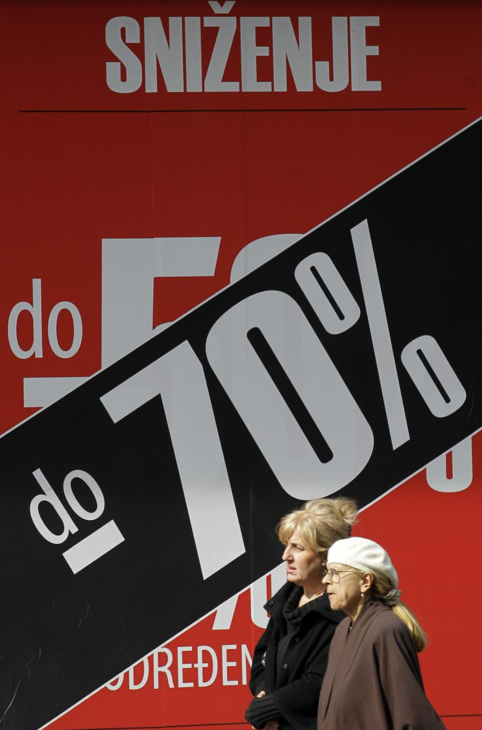 Two women pass billboard advertising an 70 percent discount on winter collection at a shop in downtown Belgrade, Serbia, Monday, March 19, 2012. Winter sales have extended well into March in Serbia and other countries in the region because of the economic crisis and a long and cold winter. (AP Photo/Darko Vojinovic)
