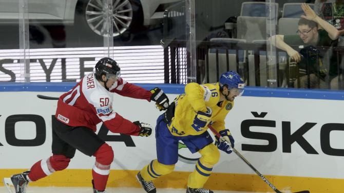Austria's Fischer fights for the puck with Sweden's Josefson as a fan reacts from the stands during their Ice Hockey World Championship game at the O2 arena in Prague