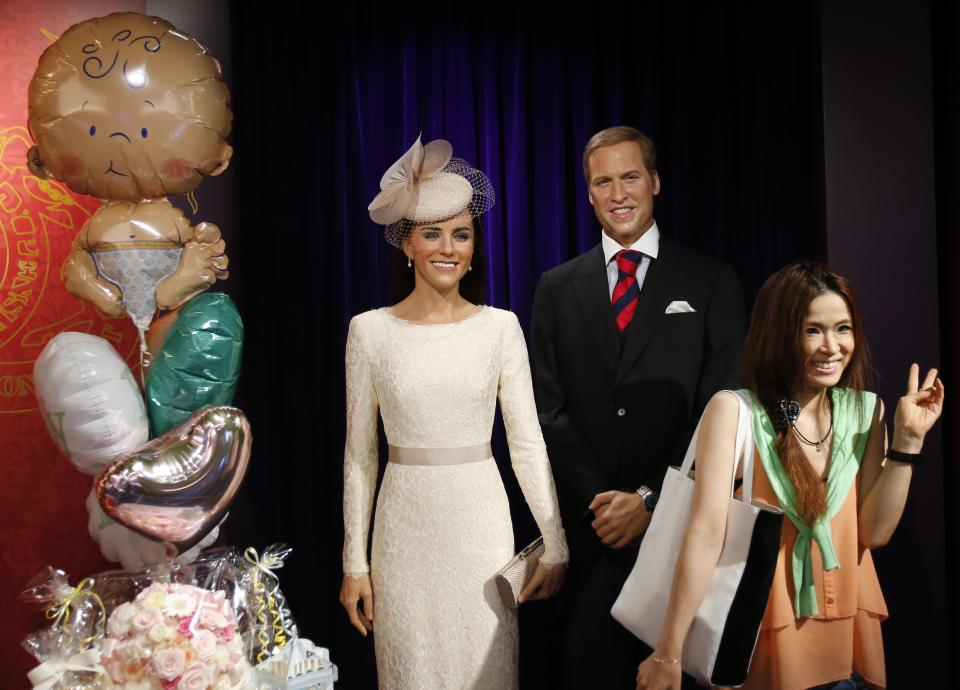 A visitor poses for a picture with wax figures of Britain's Prince William and wife Kate as balloons are displayed in celebration of the birth of the couple's first child, at Madame Tussauds in Tokyo, Tuesday, July 23, 2013. (AP Photo/Koji Sasahara)