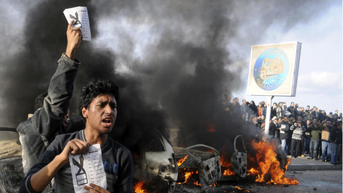 """Opponents of Egyptian President Mohammed Morsi hold pamphlets urging a """"no vote"""" on a constitutional referendum as cars burn during clashes between supporters and opponents of President Mohammed Morsi in Alexandria, Egypt, Friday, Dec. 14, 2012, a day before the referendum on the constitution.  Opposing sides in Egypt's political crisis were staging rival rallies on Friday, the final day before voting starts on a contentious draft constitution that has plunged the country into turmoil and deeply divided the nation.(AP Photo)"""
