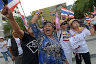 Anti-government protesters shout slogan outside the Constitutional Court in Bangkok on November 20, 2013