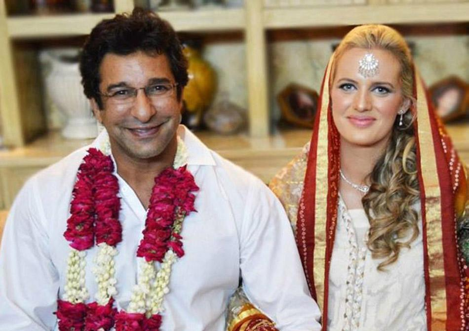 This handout photograph provided courtesy of Wasim Akram on August 21, 2013 shows former Pakistani cricket captain Wasim Akram (L) posing for a photograph with his Australian bride Shaniera Thompson d