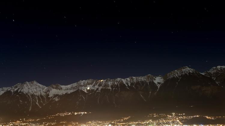 The snow covered mountain summits of Nordkette mountains are seen behind the city of Innsbruck on a long exposure picture