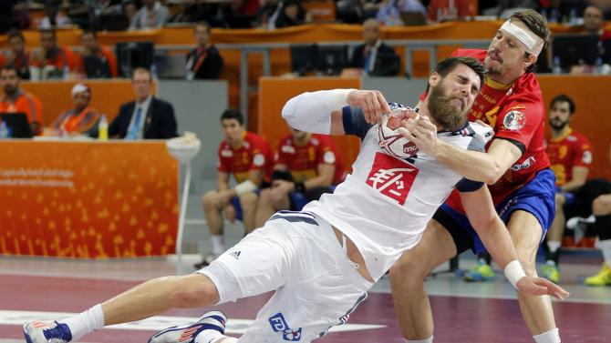 Luka Karabatic of France is blocked by Rocas of Spain during their semi-final match of the 24th Men's Handball World Championship in Doha